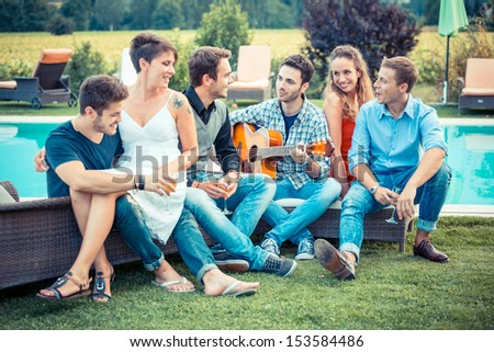 Group of Friend Singing Together next to Swimming Pool - stock photo