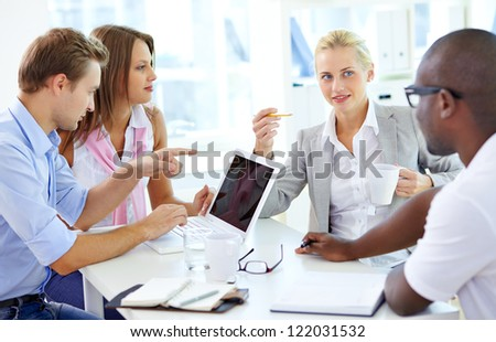 Group of friendly students or businesspeople having meeting - stock photo