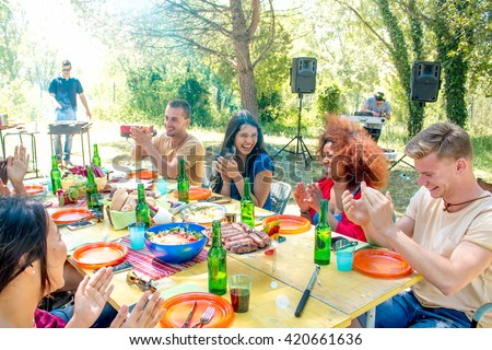 group of friends at garden barbeque lunch smiling at colorful lunch table while cooking at the smoking grill in sunny park background - weekend get-together lunch with family friends - stock photo