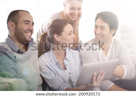 Group of friends at home using tablet in couch