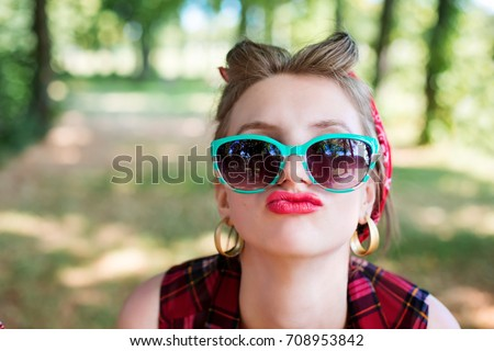 Group of friends at park having fun party. Rockabilly hen-party in park. Smiling girls holding frame