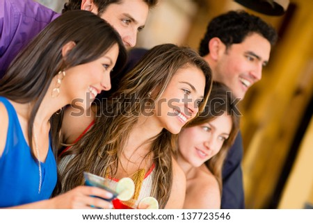 Group of friends at the bar having a drink and smiling - stock photo