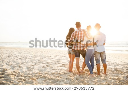 Group of friends at the beach and watching the sunset - stock photo