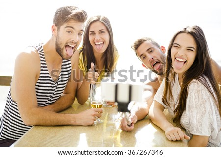 Group of friends at the beach bar and making a selfie - stock photo