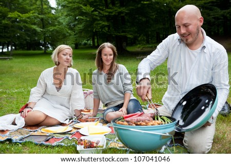 Group of friends barbecuing in park - shallow depth of field, focus on women - stock photo