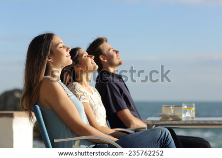 Group of friends breathing fresh air in a restaurant on the beach with the ocean in the background - stock photo