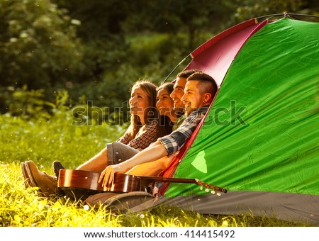 Group of friends camping.They are sitting in tent ,singing and playing guitar. - stock photo