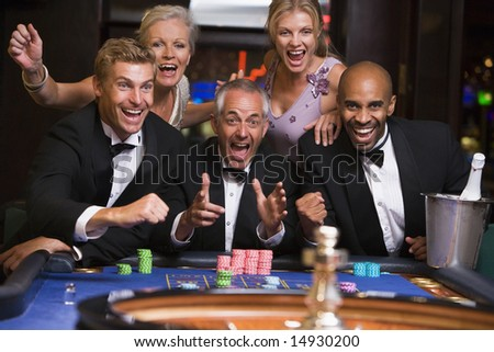 Group of friends celebrating at roulette table in casino - stock photo