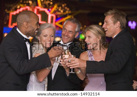 Group of friends celebrating with champagne in casino - stock photo