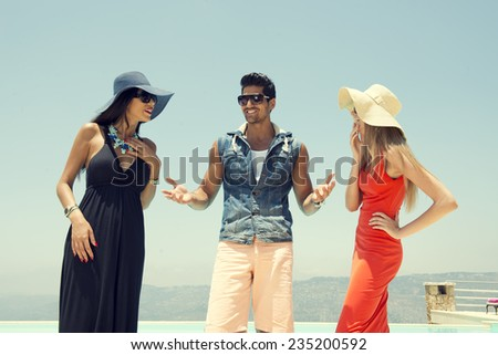 group of friends chatting and having fun at the pool, three stylish friends standing by the pool / summer holidays and vacations - stock photo