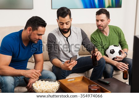 Group of friends checking their team stats on a smartphone while watching a soccer game on TV - stock photo