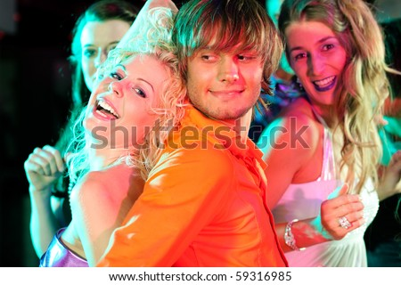 Group of friends dancing to the music in a disco club having lots of fun - stock photo