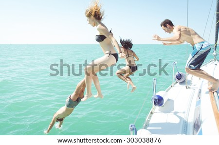 group of friends diving in the water during a boat excursion  - stock photo