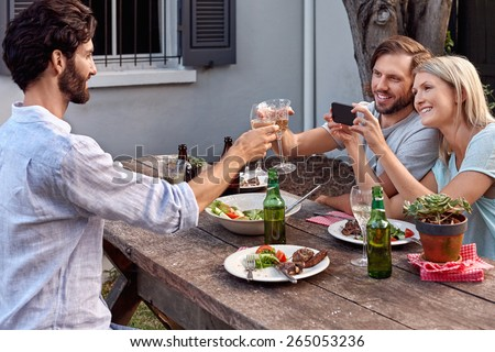 group of friends drinking cheers taking picture photos on mobile cellphone camera at outdoor garden party - stock photo