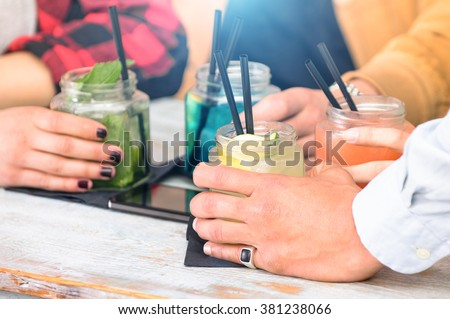 Group of friends drinking cocktails at fashion bar restaurants - Side view point of people hands with smartphone - Social gathering concept with addicted men and women - Vivid vintage filter with halo