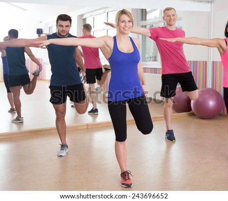 Group of friends during workout in fitness club - stock photo