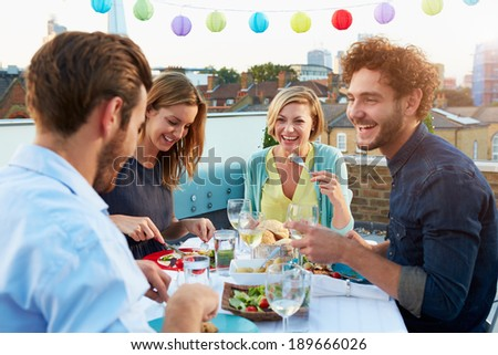 Group Of Friends Eating Meal On Rooftop Terrace - stock photo