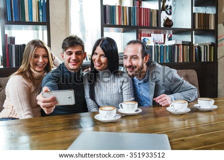 Group of friends eating out and looking at smartphone - stock photo