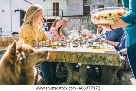 Group of friends eating outdoor. sitting outside and enjoying food. Making a celebrating toast - stock photo