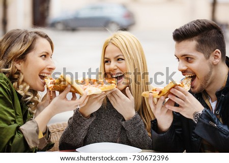 Group of friends eating pizza in a restaurant.