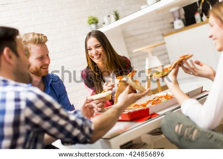Group of friends eating pizza together at home - stock photo