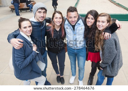 Group of friends embraced together in London. They are four girls and two boys in their twenties, friendship and lifestyle concepts, autumn clothing