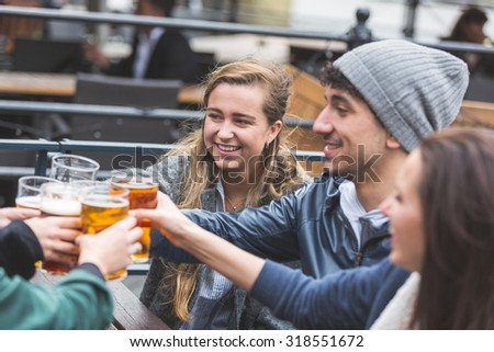 Group of friends enjoying a beer at pub in London, toasting and laughing. Close up on two girls and a boy. - stock photo