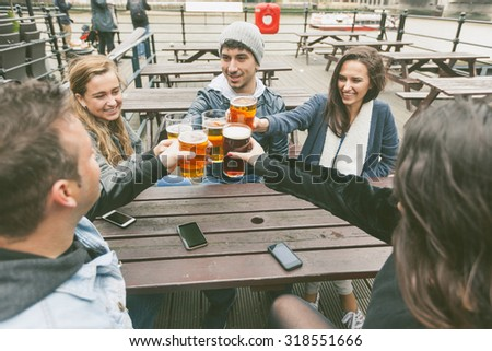 Group of friends enjoying a beer at pub in London, toasting and laughing. They are seated outside at a wood table, wearing winter clothes. - stock photo