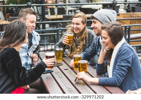 Group of friends enjoying a beer at pub in London, toasting and laughing. They are seated outside at a wood table, wearing winter clothes. Friendship and lifestyle concepts. - stock photo