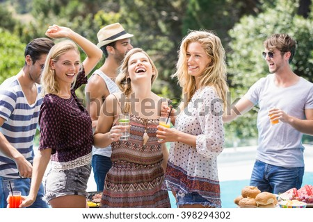 Group of friends enjoying at outdoors barbecue party near pool