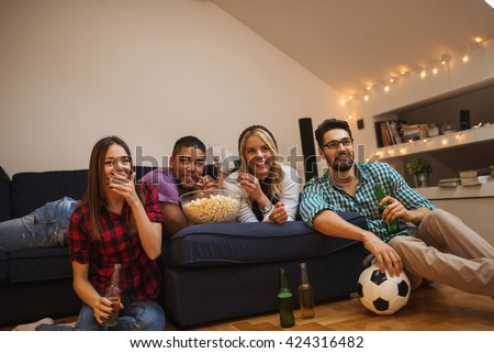 Group of friends enjoying football match together. - stock photo
