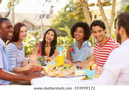 Group Of Friends Enjoying Meal At Outdoor Party In Back Yard - stock photo