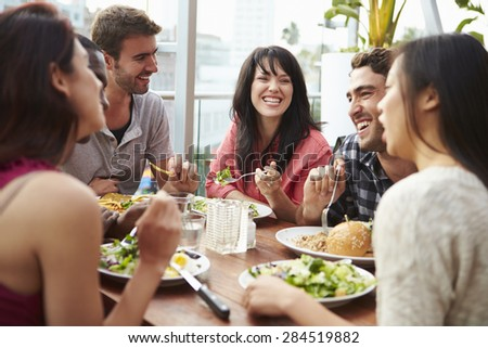 Group Of Friends Enjoying Meal At Rooftop Restaurant - stock photo