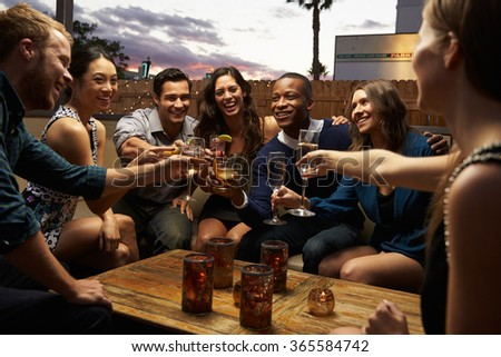 Group Of Friends Enjoying Night Out At Rooftop Bar - stock photo