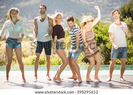 Group of friends enjoying while dancing at poolside - stock photo
