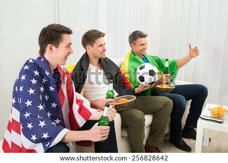 Group Of Friends From Different Nation Holding Beer Bottle Enjoying Football Game - stock photo