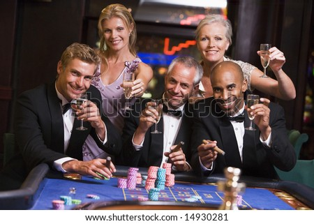 Group of friends gambling at roulette table in table - stock photo