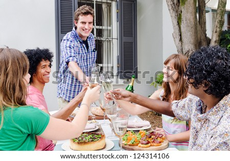 Group of friends gathered and sharing a toast of champagne, celebrating a special occasion in a casual garden outdoor setting with delicious platters of food on the table - stock photo