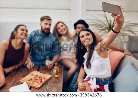 Group of friends having a party on the rooftop making a selfie to remember this perfect moment. Happy and joyful young people taking self portrait. - stock photo