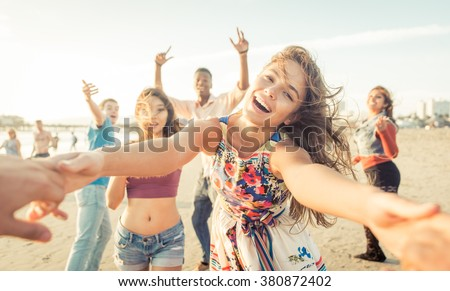 Group of friends having fun and dancing on the beach. Spring break party on the beach - stock photo
