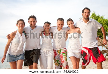 Group of friends having fun and smiling at the beach - stock photo
