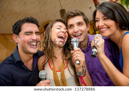 Group of friends having fun karaoke singing at the bar - stock photo