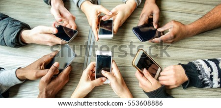 Group of friends having fun together with smartphones - Closeup of hands social networking with mobile cellphones - Wifi connected people in bar Technology and phone addiction concept - Warm filter