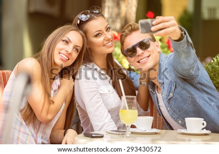 group of friends having fun with a smart phone in cafe - stock photo