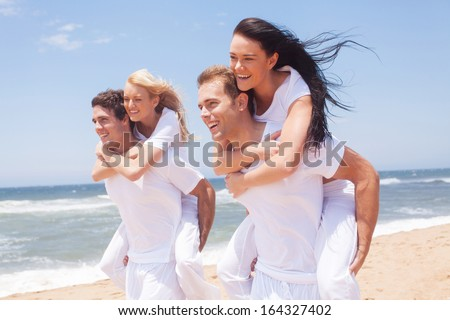 group of friends having fun with piggyback on the beach - stock photo