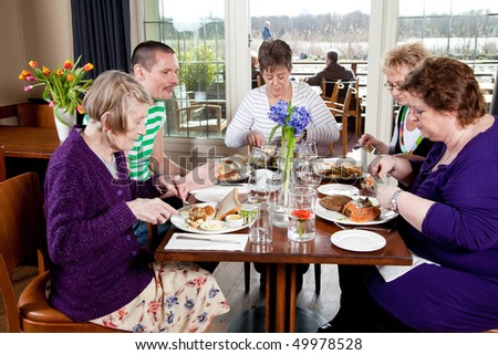 Group of friends having lunch together in a restaurant