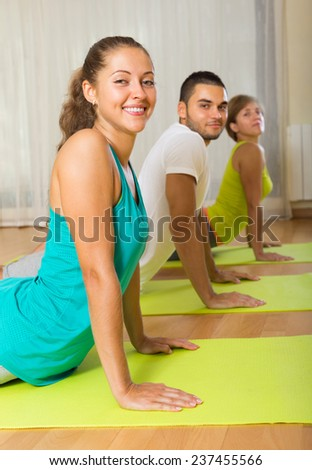 Group of friends having yoga class in sport club - stock photo