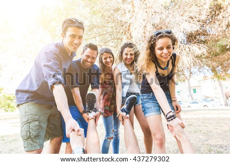 Group of friends helping someone to rise. They are looking at him and holding his hands and feet. Mixed race group. Friendship and teamwork concepts.