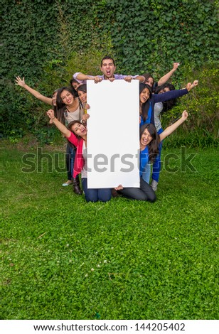 Group of friends holding blank sign outside - stock photo