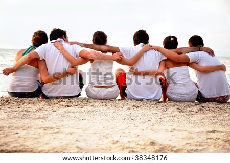 Group of friends hugging at the beach - stock photo